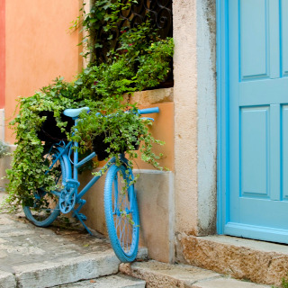 A blue bicycle in front of an orange house