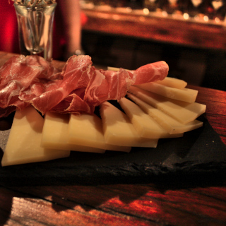 A plate with ham, cheese, and olive oil
