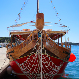 Wooden boat, painted red, with fishing nets