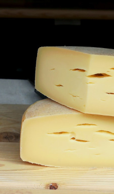 Two truckles of cheese on a table