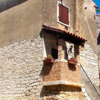 Uma casa de pedra, com janelas de madeira