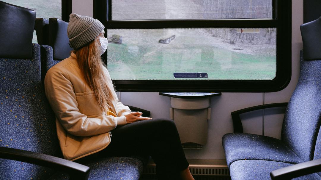 Mulher sentada perto da janela num trem, com máscara na cara