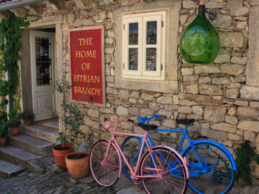 Blue and pink bicycle in front of the stone-built house