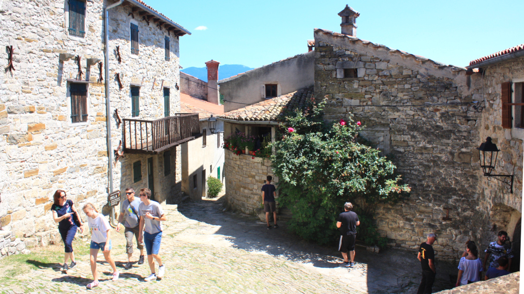 People walking among the stone houses