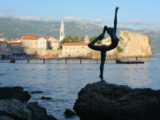 Estátua de uma dançarina em uma rocha perto do mar