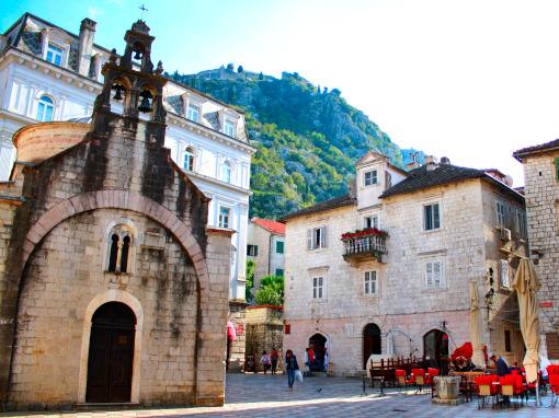 Praça da cidade com uma linda igrejinha de pedra e terraços ao redor