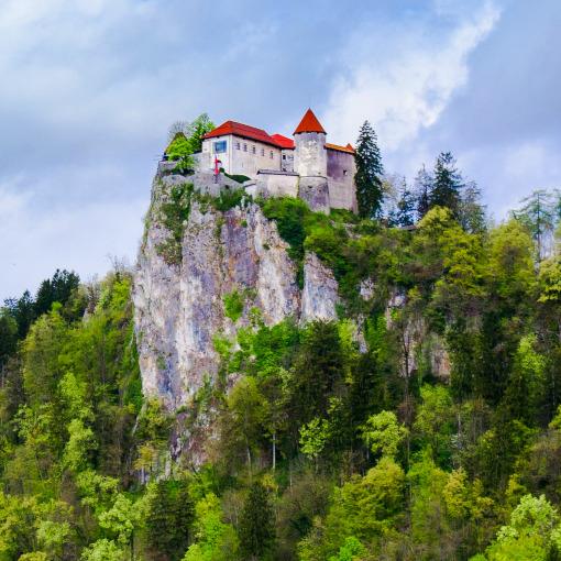 Castelo medieval no topo de um penhasco cercado por árvores