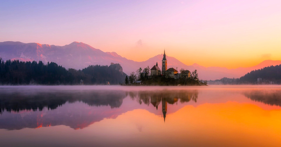 Island with a church in the middle of the lake in sunset