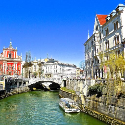 Um barco passando pelo rio com pontes na parte de trás e belos edifícios em ambos os lados