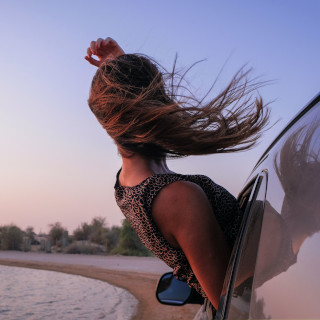 Woman leaning out of the car with wind in her hair
