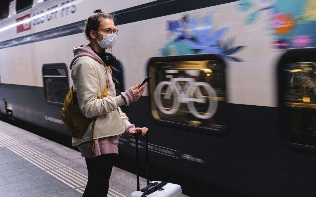 Mulher com a mâscara viajando de trem