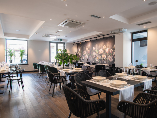 Hotel's restaurant with flowery wallpaper and black tables and chairs