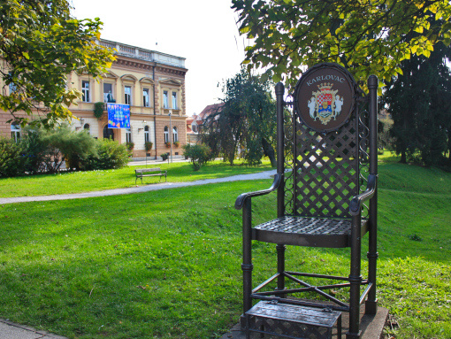 Huge metal chair in the park with a lovely ancient building in the back