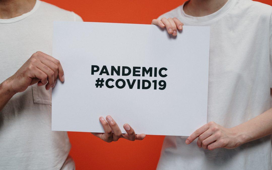 Dois homens segurando uma placa que diz coronavírus