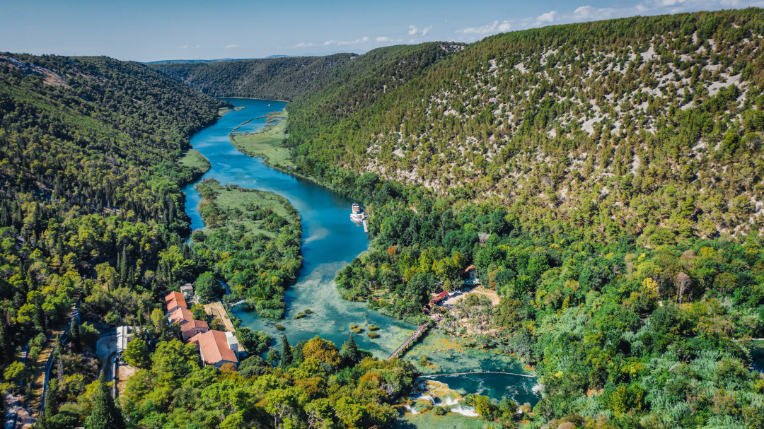 Aerial view of Krka river and its waterfalls surrounded by forest, with hills in the distance