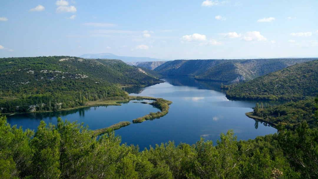 Aerial view of the Krka River canal surrounded by forest and hills