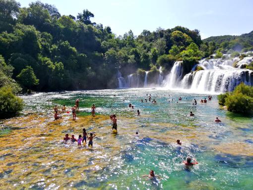 People bathing beneath a waterfall