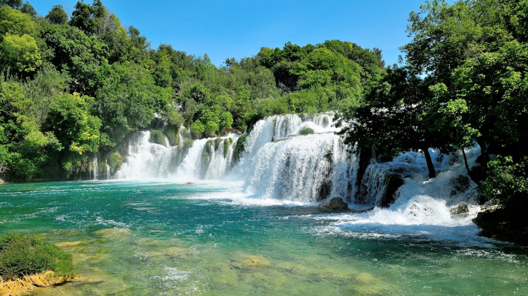 Panoramic view of waterfalls falling to the river surrounded by trees