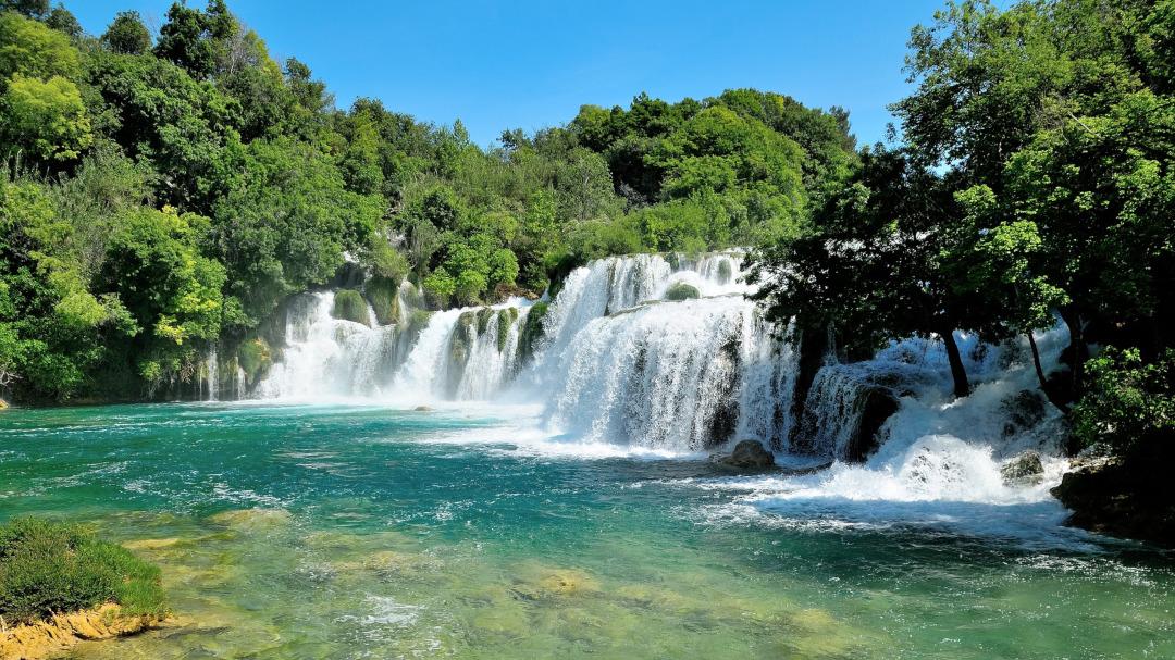 Vista panorâmica das cachoeiras caindo no rio cercadas por árvores