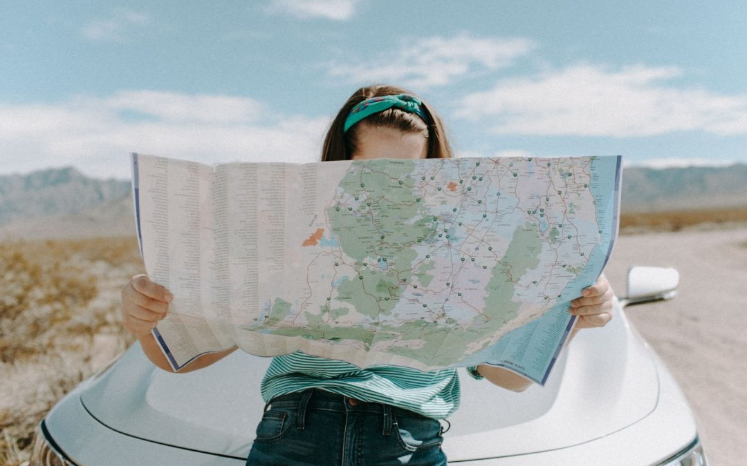 Woman holding a map on the road
